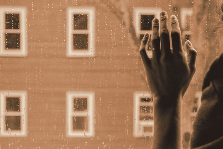 A woman hand against a window.