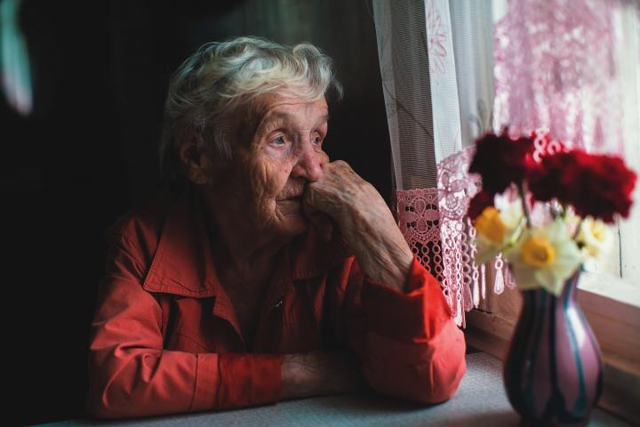 An older women sitting by a window looking outside.