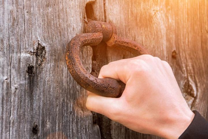 A person holding onto a door knocker.